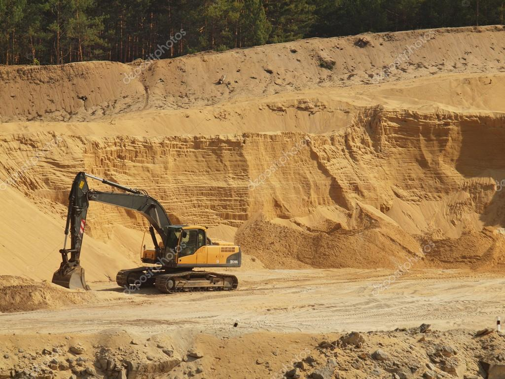 Big black orange digger in open sand mine is waiting for new shift.