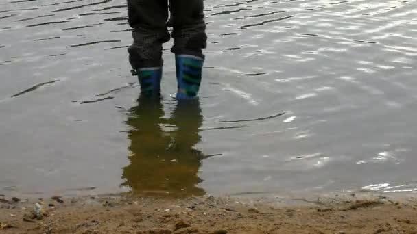 mladík je mytí gumových holínek v kalné vodě rybníka