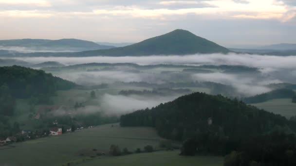 pohled do mlžné vlley pod bodem pohledu v Sasku český Švýcarsko. mlha se pohybuje mezi kopce a vrcholky stromů a dělá s sluneční paprsky jemné odlesky