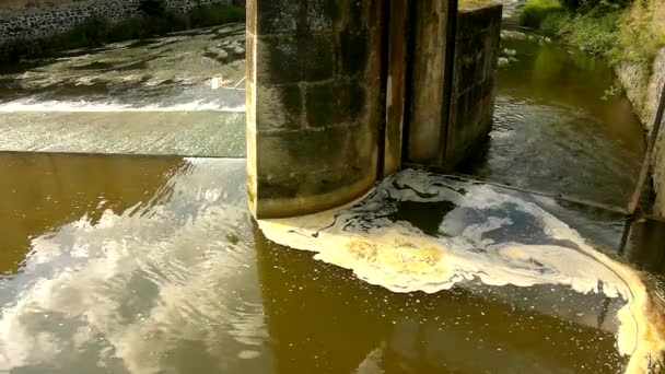 soustružení špinavé vody nad jezu na malé řece s bahnité vody. kamenné stěně splavu
