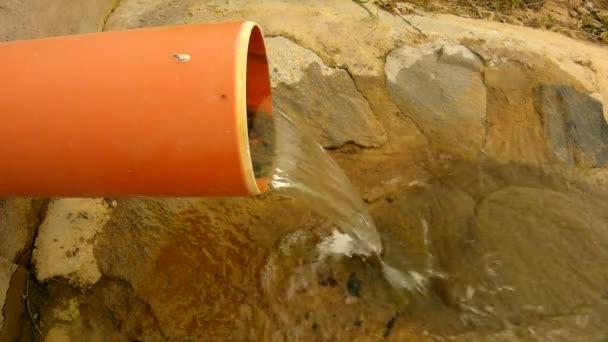 šplouchání vody z kanalizace plastové potrubí běží na balvan a bubliny vytvořit na úrovni pěnící vodu