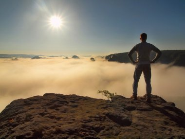 Man in shirt and jeans is standing on the peak of sandstone rock in national park Saxony Switzerland and watching over the misty and foggy morning valley to Sun. Beautiful moment the miracle of nature