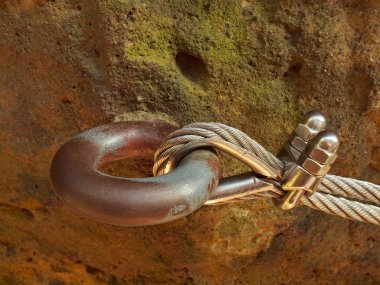 Detail of chrome screws snap hooks and grommets at and of rope. Iron twisted rope fixed together by screws snap hooks. Detail of rope end anchored at sandstone rock