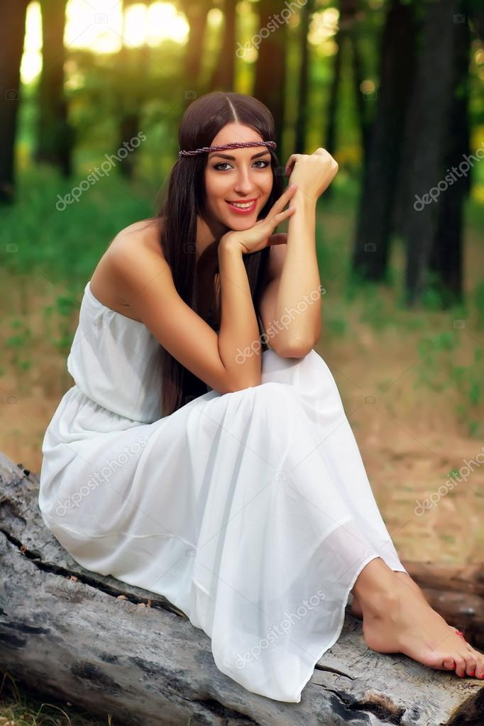 Outdoor portrait of beautiful hippie girl sitting on a dry log
