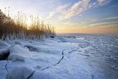 Fotografia paesaggio invernale con il lago ghiacciato e il cielo al tramonto