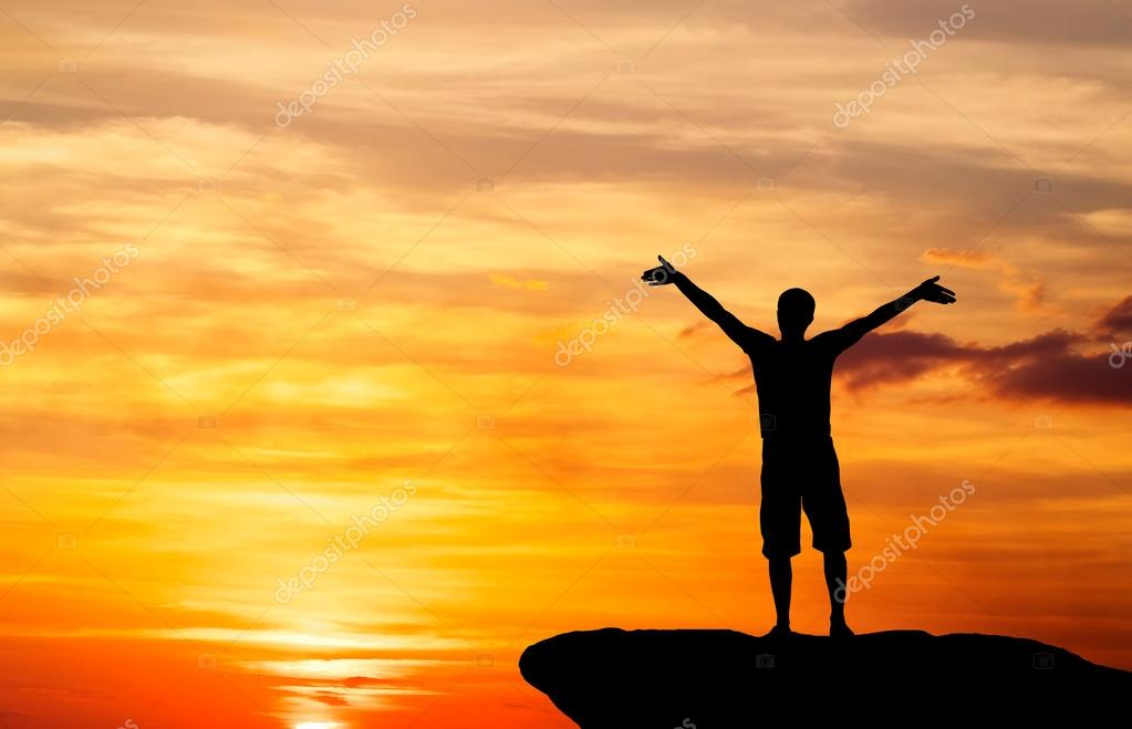 Silhouette of a man on a mountain top on fiery orange background