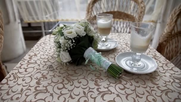 Two cups with cappuccino with wedding bouquet
