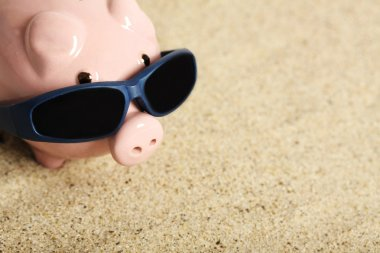 Summer piggy bank with sunglasses standing on the beach