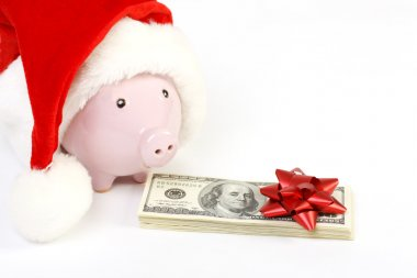 Part of piggy bank with Santa Claus hat and stack of money american hundred dollar bills with red bow on white background
