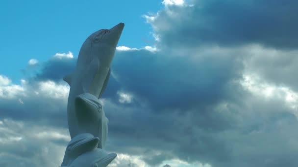 Delfin-szobor és a felhők idő telik el