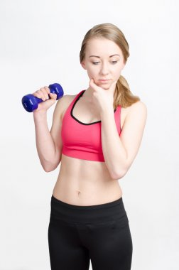 Young athletic woman wonders whether to perform physical fitness exercises