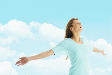 Happy Woman With Arms Outstretched Standing Against Cloudy Sky