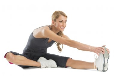 Woman Smiling While Stretching To Touch Her Toes