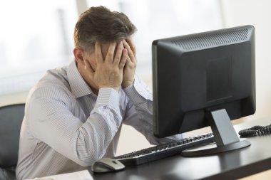 Stressed Businessman Leaning On Computer Desk