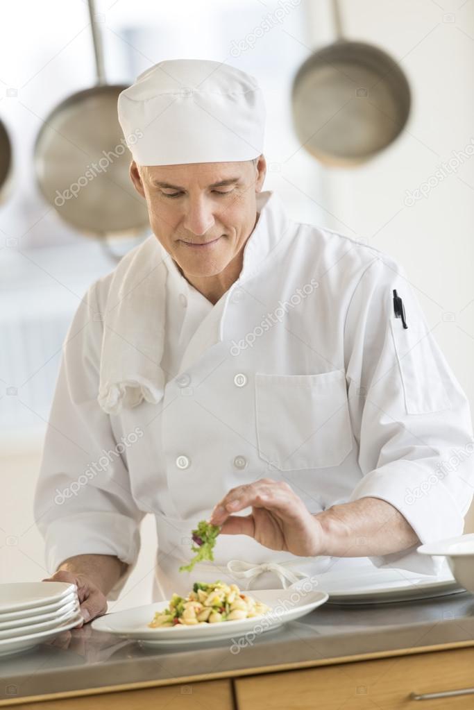 Chef Garnishing Pasta Dish In Restaurant Kitchen