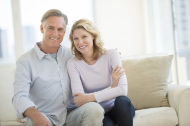 Happy Couple Sitting On Sofa In Living Room