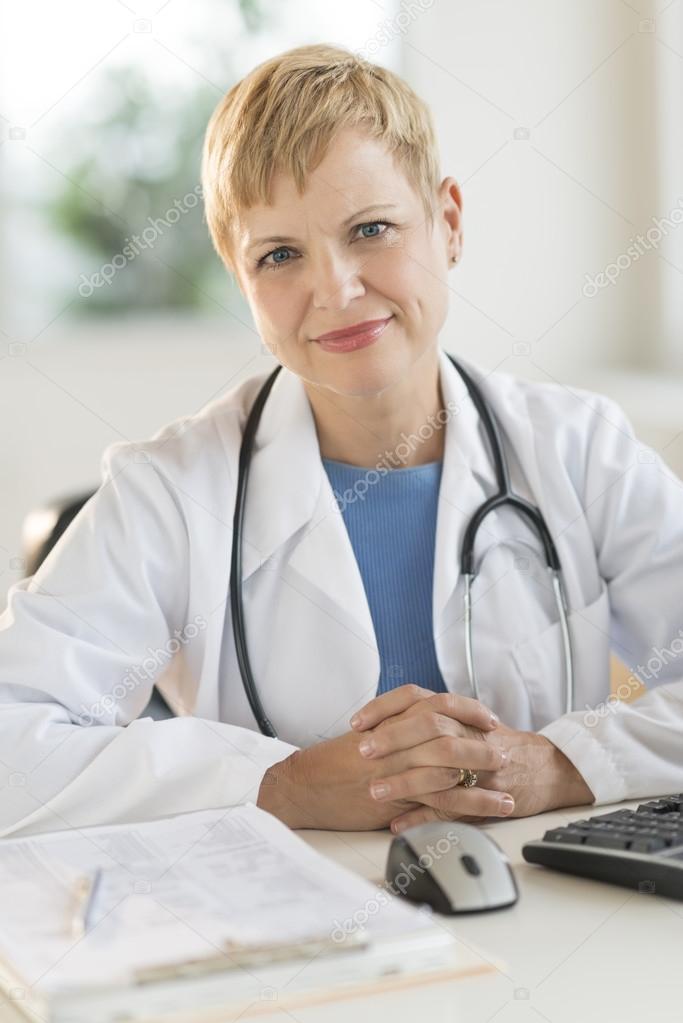Confident Female Doctor Sitting At Desk