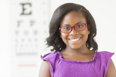 Girl Wearing Glasses Against Eye Chart In Clinic