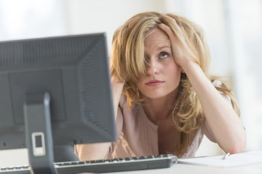 Frustrated Businesswoman With Hands In Hair At Office Desk