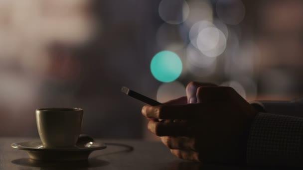 Az ember gépelés egy üzenet kávéház esti időpontban mobiltelefon használata