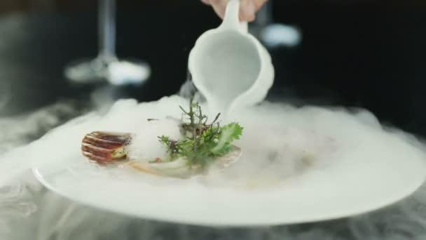 Šéfkuchař obloha mušle se suchým ledem v luxusní restauraci. detail