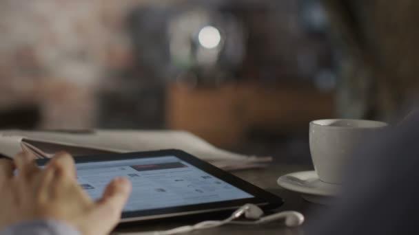muž čtení zprávy s digitálním tabletu a pití kávy