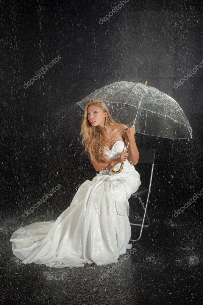 Bride with umbrella under rain in studio