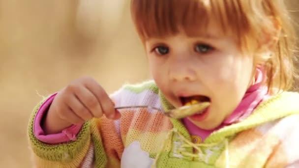 venkovní portrét: roztomilá holčička jí se lžičkou