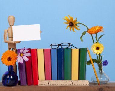 A wooden mannequin holds a card for copy space on a shelf with coloful books and flowers against a blue background. stock vector