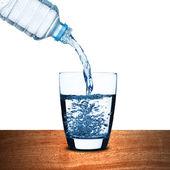 Fotografie vodu nalijte do sklenice na dřevo