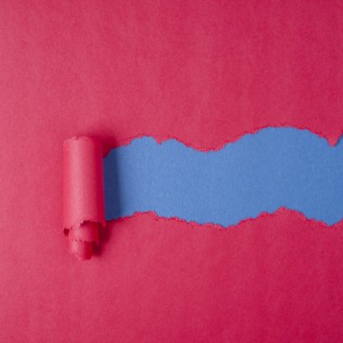 Hole ripped in red paper on blue