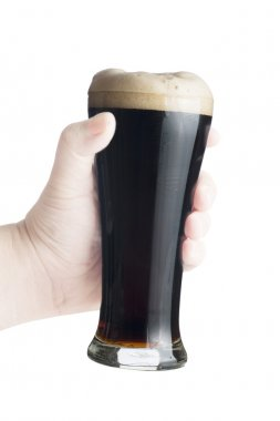 Hand holding glass of dark beer