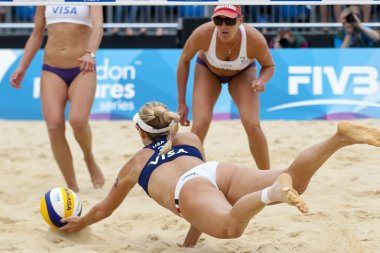 April Ross (USA) ives for the ball as Lisa Rutledge (USA) looks on during the FIVB International Beach Volleyball tournament