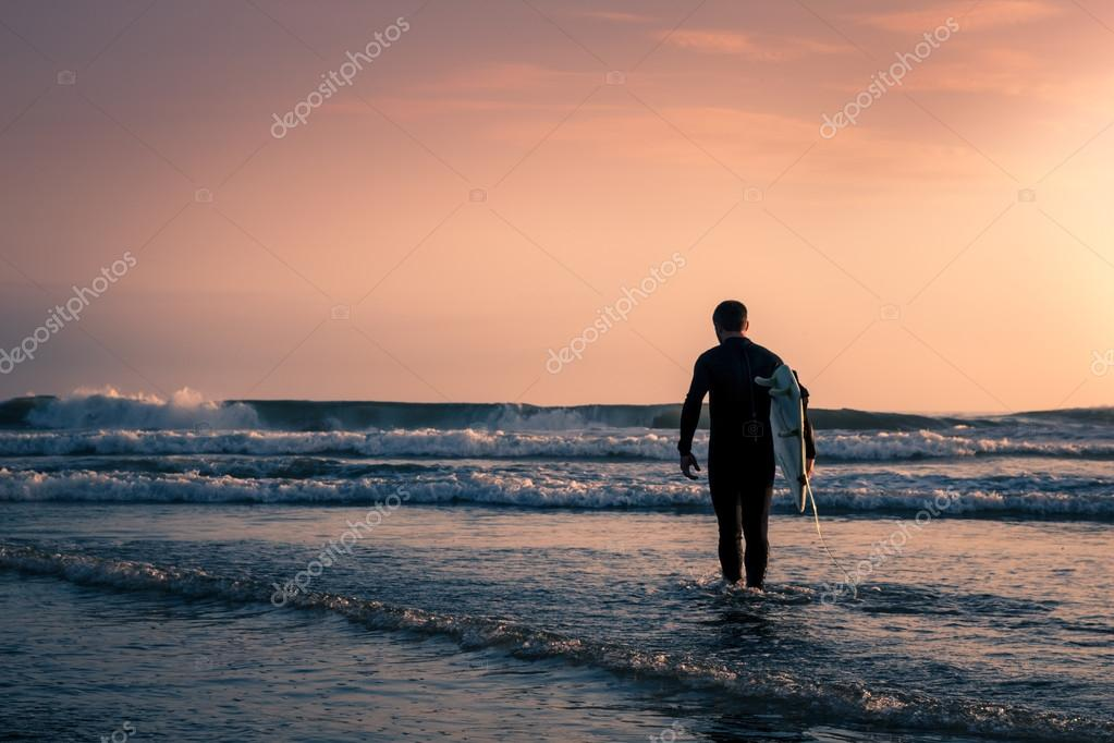 Man surfer in black diving suit with white surfboard on the beach at sunset.