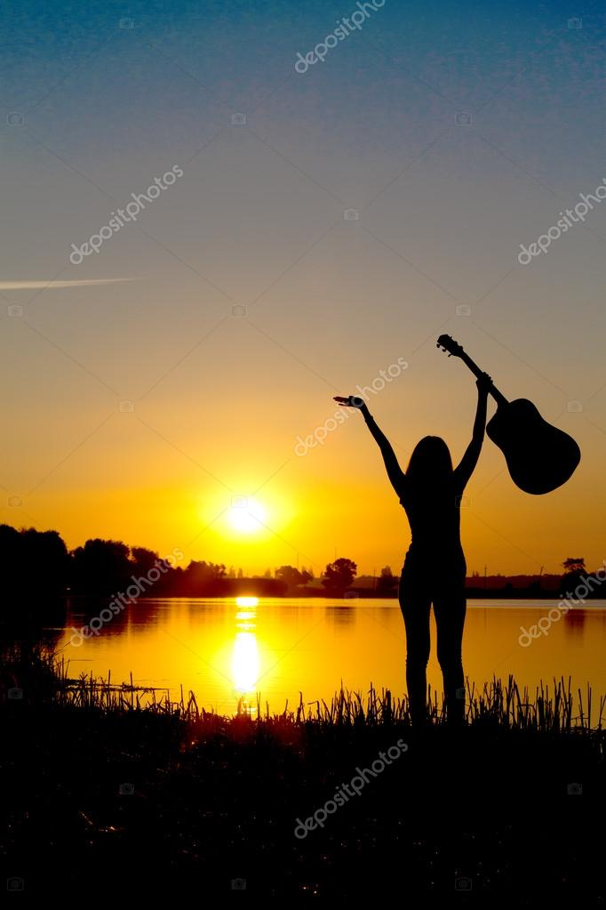 silhouette of a happy girl with a guitar on a sunrise