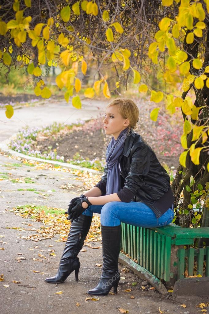 Sad young woman sit near autumn tree