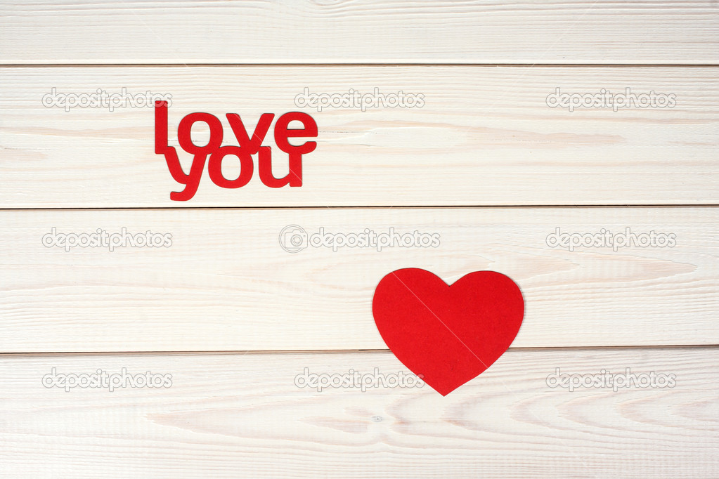Red heart symbol on a wood background with inscription love
