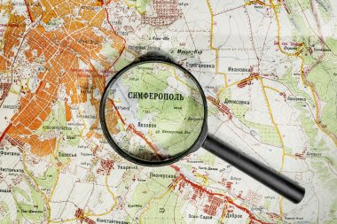 The city of Simferopol on map of Crimea through a magnifying gla