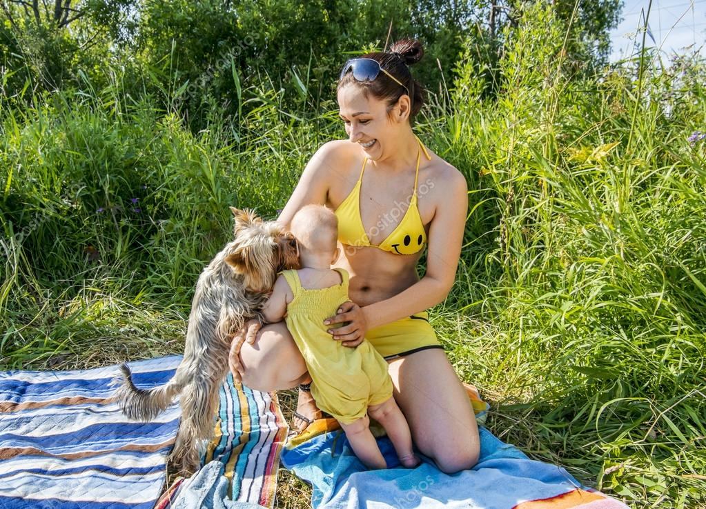 Young mother with child play with Yorkshire  Terrier at nature