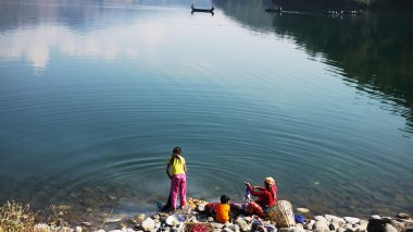 Family washing cloth in the Pokhara lake of reflection of sky and clouds in countryside pokhara, nepal, southern asia developing country