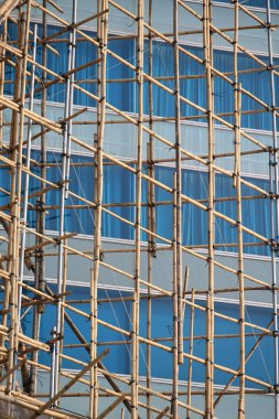 Traditional bamboo Scaffolding big project in front of modern office glass building in hong kong, Asian housing tech