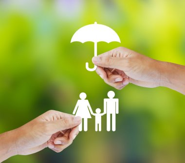 Hand holding a paper family and umbrella on green background, insurance concept