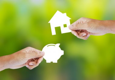 Hand holding paper piggy bank and house shape