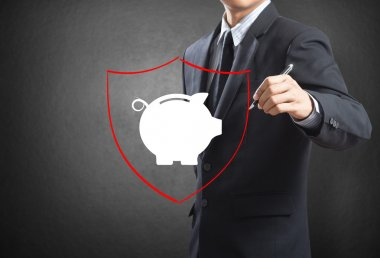 Business man drawing shield protecting piggy bank and money, insurance concept