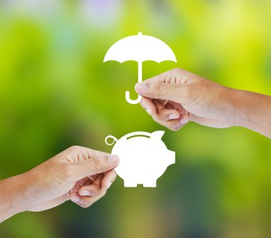 Hand holding a paper  piggy bank and umbrella