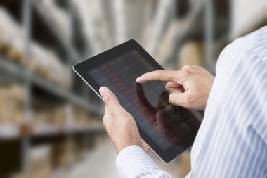 Businessman checking inventory in stock room on touchscreen tablet