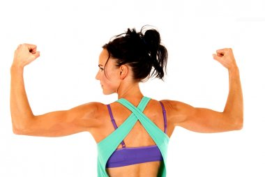 Fit woman working out flexing arm muscles from behind