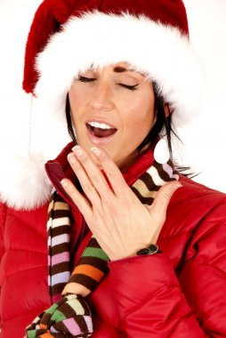 pretty female model wearing santa hat tired yawning