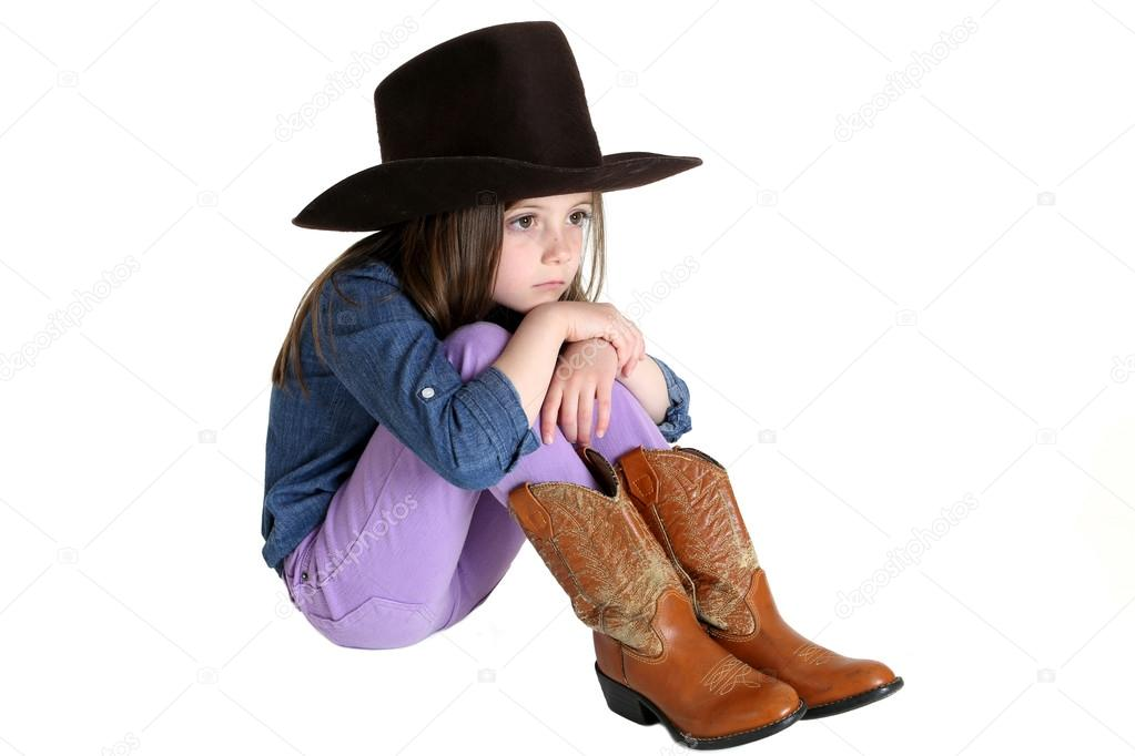 Cute Young Cowgirl Sitting With Her Knees Up Stock Photo