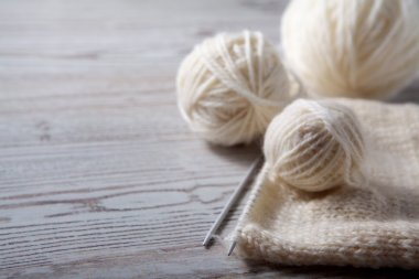 Ball of yarn and knitting on a wooden table
